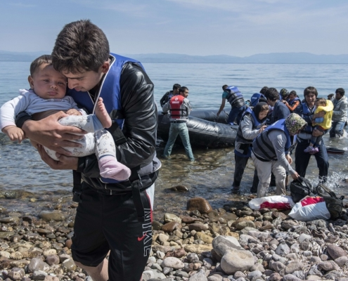 A refugee from Afghanistan carries a baby on arrival on the shores of Lesbos near Skala Skamnias, Greece on June 2, 2015. Lesbos, the Greek vacation island in the Aegean Sea between Turkey and Greece, faces massive refugee flows from the Middle East countries. Women and children are seen at the beaches and the cities of Lesbos, exhausted after the trip over the Aegean Sea. Some children are even born on the flight from war. Last week alone over 2500 refugees arrived on the island, where they will be registred by Greek authorities. After registration most refugees are left on their own.  AFP PHOTO / SCANPIX DENMARK / SOEREN BIDSTRUP +++ DENMARK OUT        (Photo credit should read SOEREN BIDSTRUP/AFP/Getty Images)